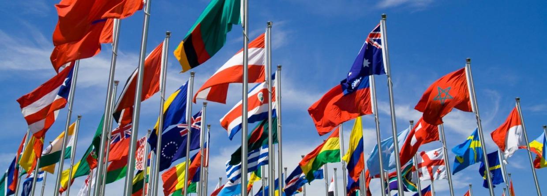 Diverse vlaggen tegen wolkenlucht